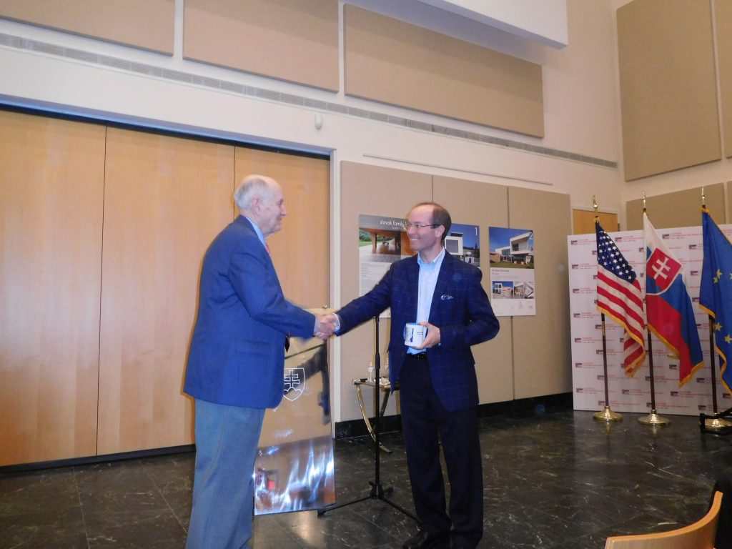 Amb. Ted Russell (Ret.) and Dr. James Krapfl shaking hands.
