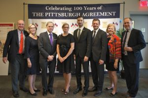 "Group photo of the people named in the caption standing in front of a ""Celebrating 100 years of the Pittsburgh Agreement"" banner."