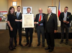 Inidividuals named in the caption are together holding the Pittsburgh Agreement document kept in a preservation frame.